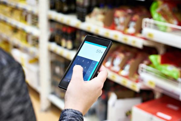 Shopper using calculator on smartphone in supermarket