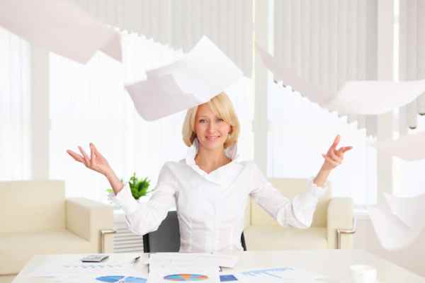 Professional woman throwing up papers in office