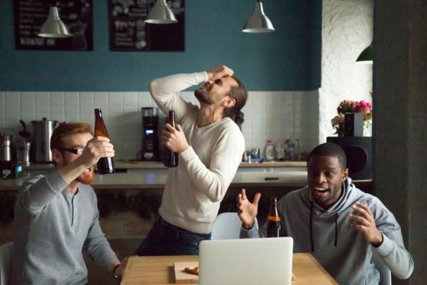 Group of men watching team lose on laptop