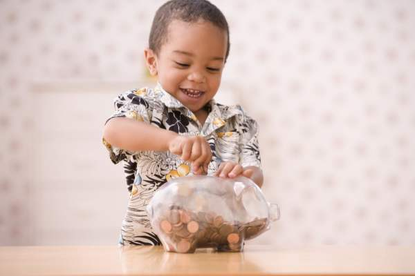 Little boy putting coins in glass piggy bank