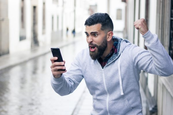 Man celebrating a betting win on his phone
