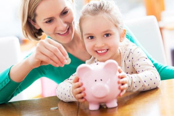 Mother and young daughter saving money in piggy bank