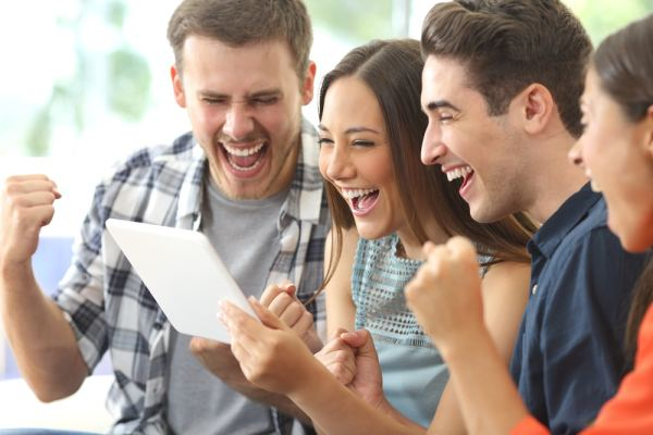 Group of friends celebrating a win on a tablet