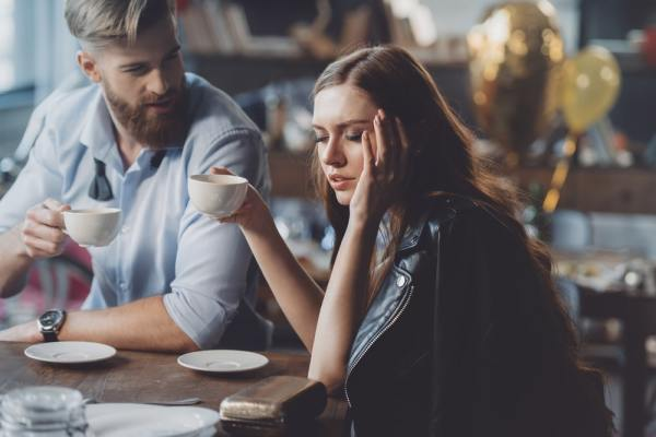 Man having coffee with hungover woman