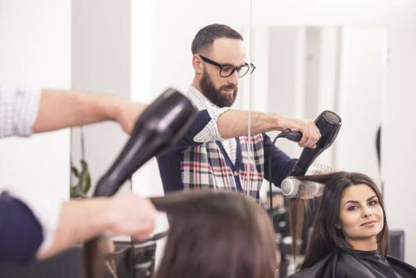 Male hairdresser styling womans hair