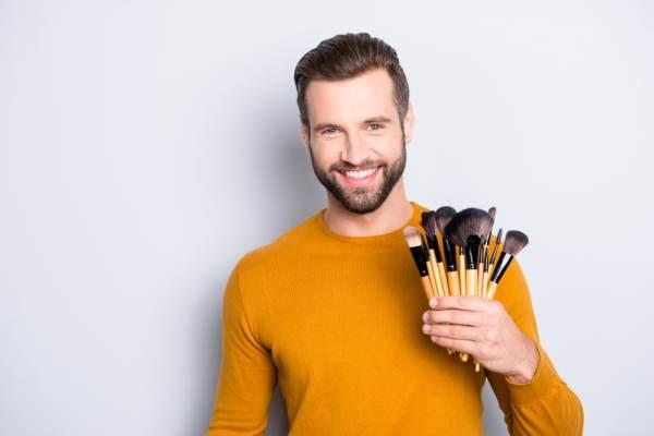 Man holding makeup brushes