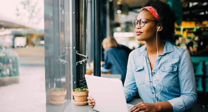 Stay motivated as a freelancer by changing your workspace like this lady working in a cafe