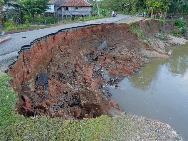 Salah satu jalan OKU-Ogan Ilir di tepi Sungai Ogan yang amblas. Foto Taufik Wijaya