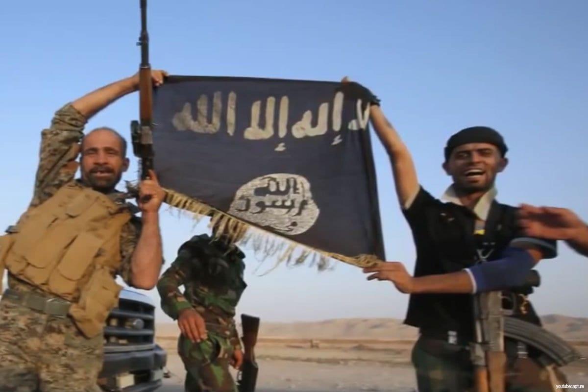 Militantes del Daesh izan su bandera.