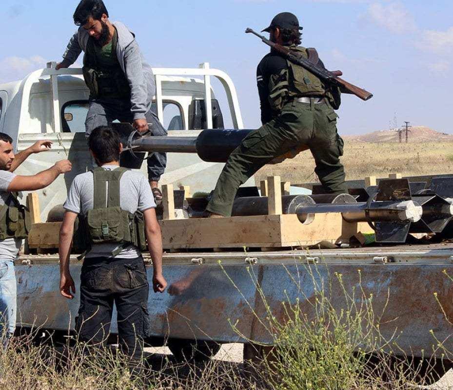 Rebeldes sirios se disponen a lanzar un proyectil contra las fuerzas del régimen en Alepo.