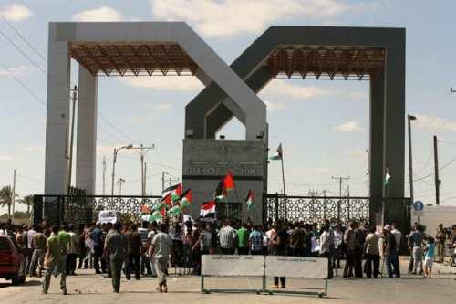 """Un grupo de palestinos ondean una bandera nacional palestina y otra egipcia mientras participan en una marcha llamando a las autoridades egipcias a abrir el paso de Rafah, a las puertas del paso de Rafah en el sur de la Franja de Gaza el 16 de Septiembre de 2013. El Cairo cerró completamente el paso de Rafah la principal ventana gazatí al mundo, la semana pasada después de que dos atacantes hicieran explosionar sendos vehículos contra instalaciones de seguridad adyacentes a la zona fronteriza, matando a seis soldados egipcios. Ashraf al-Qidra, portavoz del Ministerio de Sanidad dirigiod por Hamás en la Franja, asegura que más de 1.00 0 enfermos necesitan urgentemente asistencia médica en Egipto y otros países. El cierre de Rafah, asegura Al-Qidra, está afectando también a la importación de medicinas y a la llegada de especialistas a Gaza. En las pancartas de la imagen se puede leer: """"Los gazatíes estamos privados de energía y gasoil"""" y """"Exigimos la apertura por parte de Egipto para encontrar alternativas a los túneles"""". Foto de Eyad Al-Baba."""