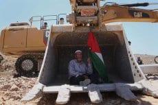 RAMALA, PALESTINA: Un hombre sostiene una bandera palestina mientras protesta contra la construcción de asentamientos iraelíes en Cisjordania, cerc de la aldea palestina de Deir Qaddís, en los alrededores de Ramala