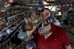 HEBRÓN, PALESTINA: Un comerciante local utiliza cristales pintados para decorar su negocio.