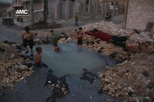 Syrian-children-swim-in-hole-on-street-left-by-airstrikes-1