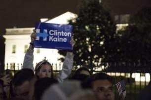 WASHINGTON: Una chica enseña una pancarta de apoyo a los Demócratas entre la multitud de partidarios de Trump y Clinton concentrados frente a la Casa Blanca en espera de los resultados electorales. (Samuel Corum/Agencia Anadolu)