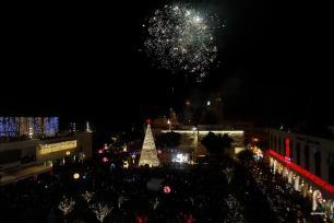 BELÉN, CISJORDANIA- Fuegos artificiales que prenden el alumbrado de un árbol de Navidad, también se ve el pesebre cerca de la iglesia de la natividad