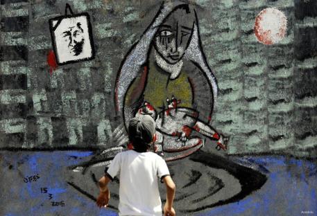 SANAA, YEMEN: Un chico yemení mira un mural que fue pintado por estudiantes para simbolizar la guerra en curso en el país en la Universidad de Sanaa.