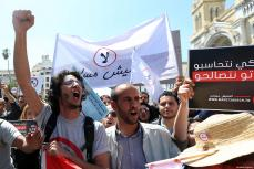 La gente sostiene pancartas durante una protesta contra el proyecto de ley del gobierno sobre la reconciliación económica y financiera en Túnez, Túnez, el 29 de Abril de 2017 [Yassine Gaidi / Agencia Anadolu]