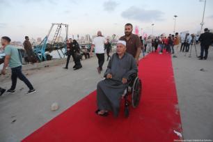 Un anciano en silla de ruedas durante la ceremonia de inauguración del tercer festival anual de cine sobre derechos humanos de Gaza, el 12 de Mayo de 2017. [Imagen: Mohammad Asad / Middle East Monitor]