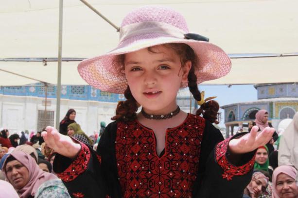 Jerusalén, PALESTINA- Una niña asiste a las oraciones en Al-Aqsa con ropa tradicional palestina y un sombrero rosa a la útlima moda