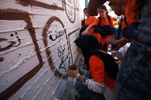 Los niños y niñas palestinos pintan en una pared de la escuela en un viaje de familiarización organizado por UNRWA en el campamento de Askar Al-Jadeed en Nablus, Cisjordania el 23 de agosto de 2017 [Nedal Eshtayah / Agencia Anadolu]