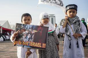 """Niños muestran un cartel que dice """"Israel vete al infierno"""" y una de ellos lleva un pañuelo en el que se lee salva Palestina durante la manifestación para apoyar a Palestina en el Monumento Nacional en Yakarta, Indonesia, 17 de diciembre de 2017 [Agencia Nani Afrida / Anadolu]"""