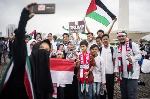 """Un grupo de manifestantes se toma una selfie con una pancarta en la que aparece inscrito """"Trump deja tu racismo"""" y una bandera palestina, en la manifestación para apoyar a Palestina en el Monumento Nacional en Yakarta, Indonesia, 17 de diciembre de 2017 [Anton Raharjo / Agencia Anadolu]"""