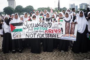 """Manifestantes sostienen la pancarta """"Jerusalén para Palestina"""" en la manifestación para apoyar a Palestina en el Monumento Nacional en Yakarta, Indonesia, 17 de diciembre de 2017 [Anton Raharjo / Agencia Anadolu]"""