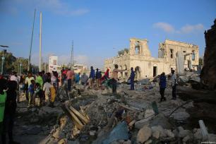 Un grupo de personas inspecciona el lugar tras los ataques perpetrados cerca del edificio de la Agencia Nacional de Inteligencia y Seguridad de Somalia (NISA) en Mogadiscio, Somalia, 24 de febrero de 2018 [Agencia Sadak Mohamed / Anadolu].