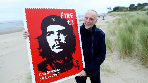 El artista irlandés Jim Fitzpatrick con una imagen promocional de un sello con su famosa imagen de Che Guevara [Irish Times]