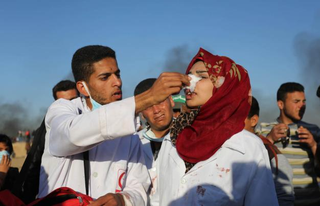 """La voluntaria palestina Rezzan en-Neccar (C) cura a un palestino herido por las fuerzas de seguridad israelíes durante las manifestaciones del """"Día de la Tierra"""", que conmemora el asesinato de seis palestinos por las fuerzas israelíes en 1976, en Khan Yunis, Gaza, 1 de abril de 2018 (Ashraf Amra- Anadolu Agency)"""