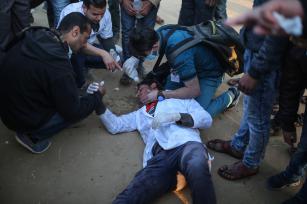"""Un médico palestino, herido por los ataques israelíes, es socorrido por otros compañeros, durante el """"Día de la Tierra"""", que conmemora el asesinato de seis palestinos por las fuerzas israelíes en 1976, en Khan Yunis, Gaza, 1 de abril de 2018 (Ashraf Amra- Anadolu Agency)"""