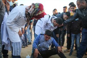 """Un médico ayuda a palestinos heridos durante el """"Día de la Tierra"""", que conmemora el asesinato de seis palestinos por las fuerzas israelíes en 1976, en Khan Yunis, Gaza, 1 de abril de 2018 (Ashraf Amra- Anadolu Agency)"""