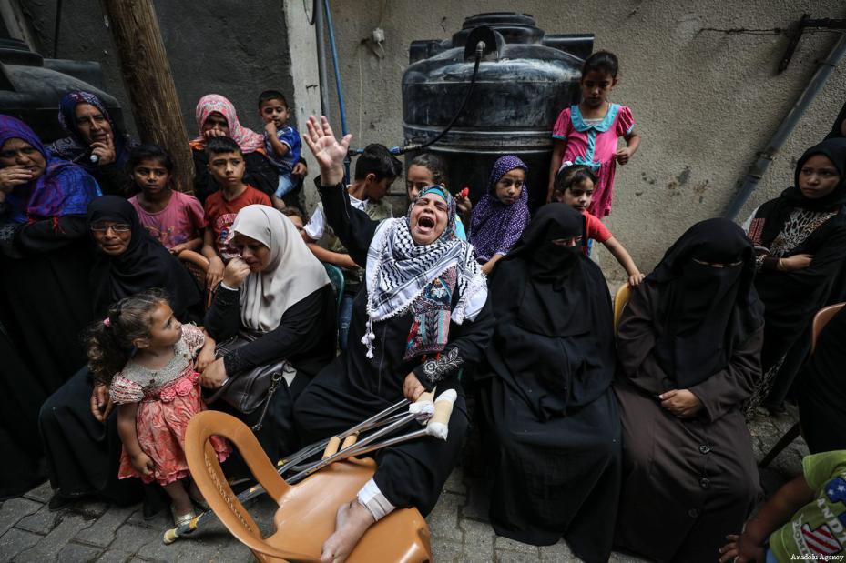 """Una mujer llora durante el funeral de de Razan Ashraf al-Najjar, 21 años, una paramédica asesinada a tiros por las fuerzas israelíes mientras asistía a los manifestantes heridos durante las protestas de """"Gran Marcha del Retorno"""" el viernes, en el barrio de Huzaa de Jan Yunis, Gaza, 2 de junio de 2018 [Agencia Mustafa Hassona / Anadolu]"""