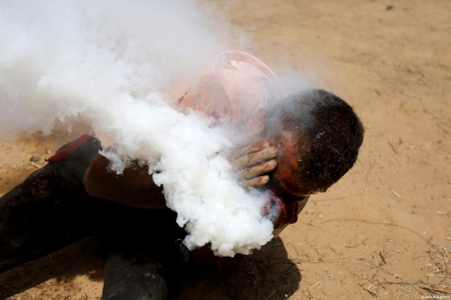 Haitham Abu Sabla, de 23 años, corre tras ser alcanzado con un bote de gas lacrimógeno en la cara durante una manifestación en conmemoración del Naksa, en la frontera entre Gaza en Israel el pasado 8 de junio de 2018 [Ashraf Amra / Agencia Anadolu]