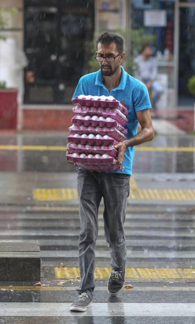 Un hombre porta huevos caminando bajo una lluvia torrencial en Ankara, Turquía, 31 de julio de 2018 [Agencia Celal Güneş / Anadolu]