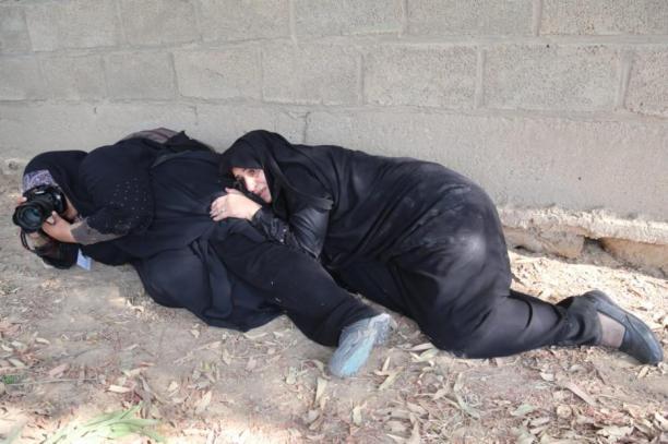 Una fotoperiodista hace una foto mientras se protege cuerpo a tierra después del atentado contra una marcha militar en la ciudad de Ahwaz el 22 de septiembre de 2018.(Mehdi Pedramkhoo - Agencia Anadolu)
