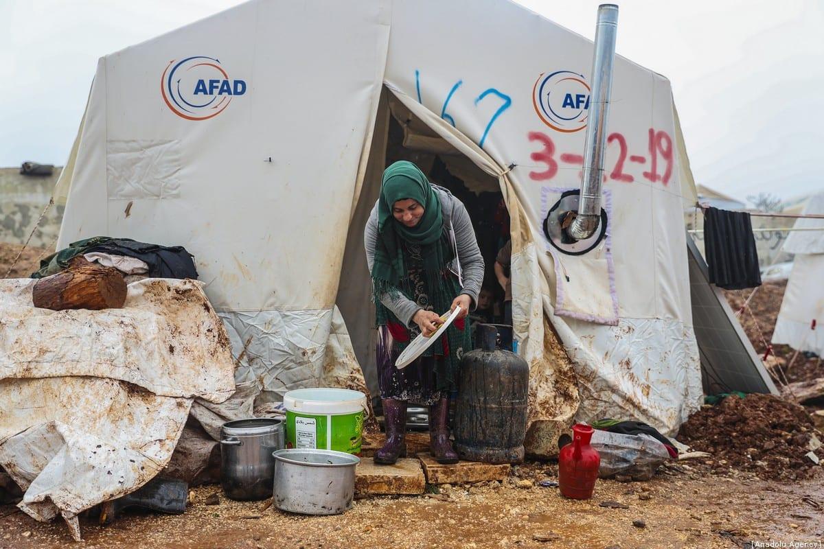 Se ve a una mujer siria frente a su tienda de campaña en un campamento donde se alojan familias sirias, que se han visto obligadas a desplazarse debido a los ataques llevados a cabo por el régimen de Assad y Rusia, en Idlib, Siria, el 10 de enero de 2020 [Agencia Esra Hacioğlu / Anadolu]