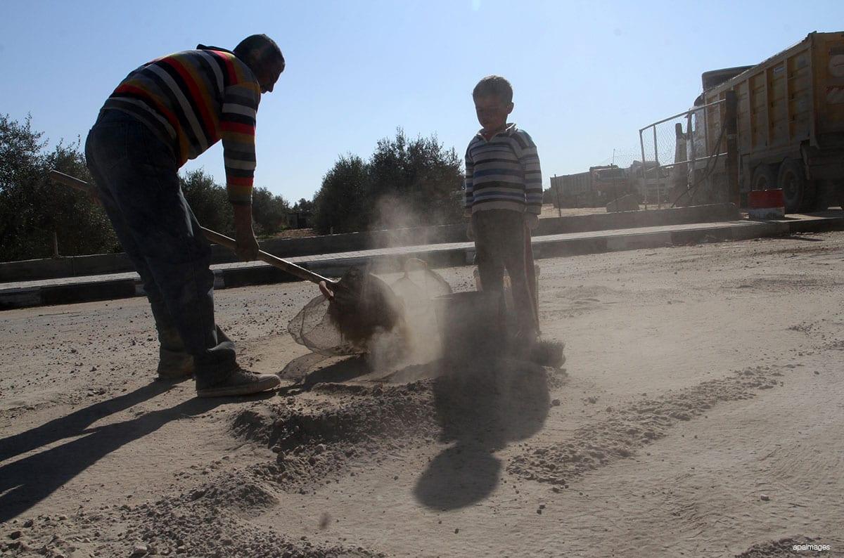 Un hombre palestino recoge la grava que cae de los camiones cargados de cemento después de que ingresó por el cruce de Kerem Shalom en Rafah, para venderla a los clientes, en Gaza