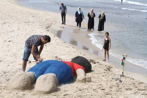 Artista palestino se gana la vida esculpiendo arena recrea la imagen icónica de cuando el cuerpo del refugiado sirio Alan Kurdi llegó a las costas turcas