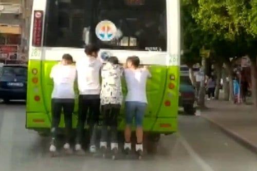 Patinadores turcos dan un paseo detrás de un autobús