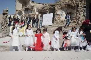 Los niños se reúnen mientras se terminan los preparativos para la misa a la que asistirá el Papa Francisco en la plaza de la iglesia de Hosh al-Bieaa en Mosul, Irak, el 7 de marzo de 2021 [Osama Al Maqdoni / Agencia Anadolu].