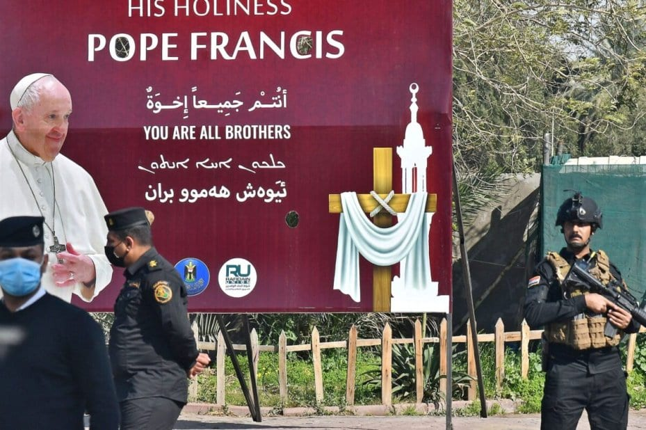 La seguridad iraquí frente a un enorme cartel de bienvenida al Papa Francisco en Bagdad, tras su llegada el 5 de marzo de 2021, al inicio de la primera visita papal a Irak [VINCENZO PINTO/AFP via Getty Images].