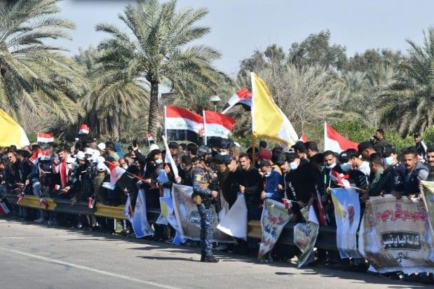 Los iraquíes se alinean en la carretera que conduce al aeropuerto de Bagdad mientras dan la bienvenida al pontífice a su llegada el 5 de marzo de 2021 [VINCENZO PINTO/AFP vía Getty Images].