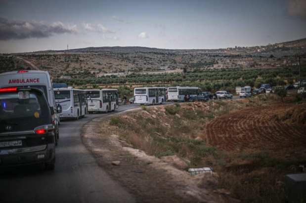 Personas se trasladan en un autobús a un sitio de casas de briquetas construido por Turquía en Idlib, Siria, después de haber sido desplazadas a la fuerza por el régimen de Assad desde la aldea de Umm Batinah en Quneitra, Siria, el 22 de mayo de 2021. 30 familias de un total de 150 personas fueron desplazadas [Muhammed Said/Anadolu Agency].