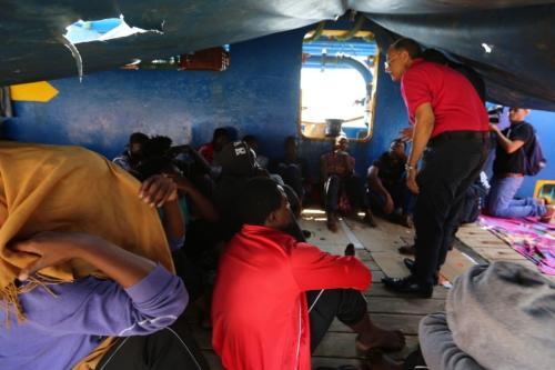 """Imigrantes africanos sentados a bordo do navio """"Sarost 5"""", atracado no sul da Tunísia, no porto de Zarzis, em 1 de agosto de 2018. [Fathi Nasri/ AFP/ Getty]"""