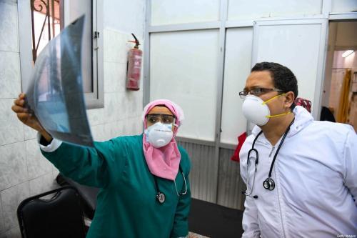 Médicos egípcios verificam radiografia de paciente na unidade de doenças infecciosas do hospital de Imbaba, na capital Cairo, em 19 de abril de 2020, durante a nova crise de pandemia de coronavírus [Ahmed Hasan/ AFP via Getty Images]