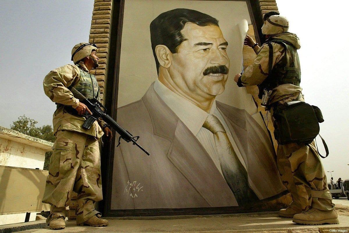 Militar rasga pôster do presidente iraquiano Saddam Hussein em 21 de março de 2003 em Safwan, Iraque. [Chris Hondros/ Getty Images]