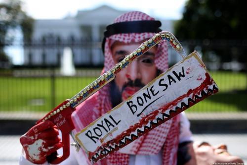 Manifestantes veste máscara do príncipe herdeiro saudita Mohammed bin Salman e exibe uma serra ensanguentada, em protesto ao assassinato do jornalista Jamal Khashoggi, em Washington DC, Estados Unidos, 2 de outubro de 2018 [Win McNamee/Getty Images]