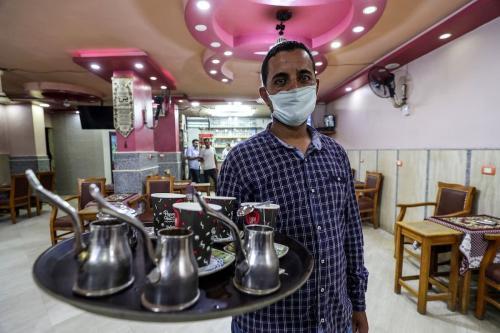 Garçom serve em um café na capital egípcia, Cairo, em 27 de junho de 2020, depois que as autoridades relaxaram as medidas de bloqueio para conter a propagação do coronavírus [Mohamed El-Shahed/ AFP via Getty Images]